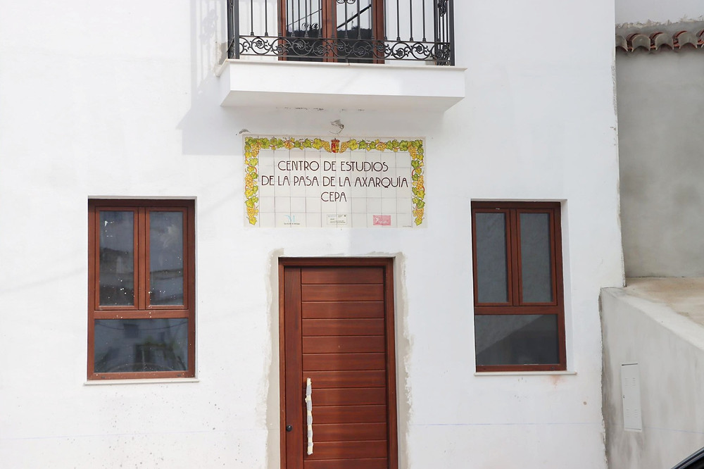 New wooden door with windows on each side and a tiled sign above. A balcony sits at the top.