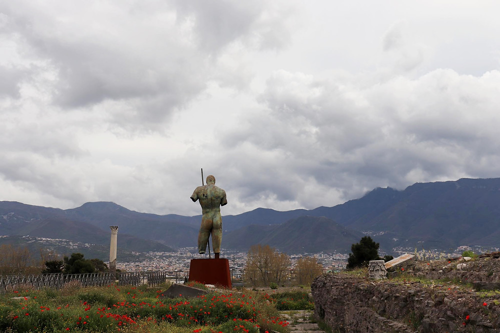 Large statue holding a spear with broken legs and arms made of iron standing overlooking the modern city below with dark clouds overhead.