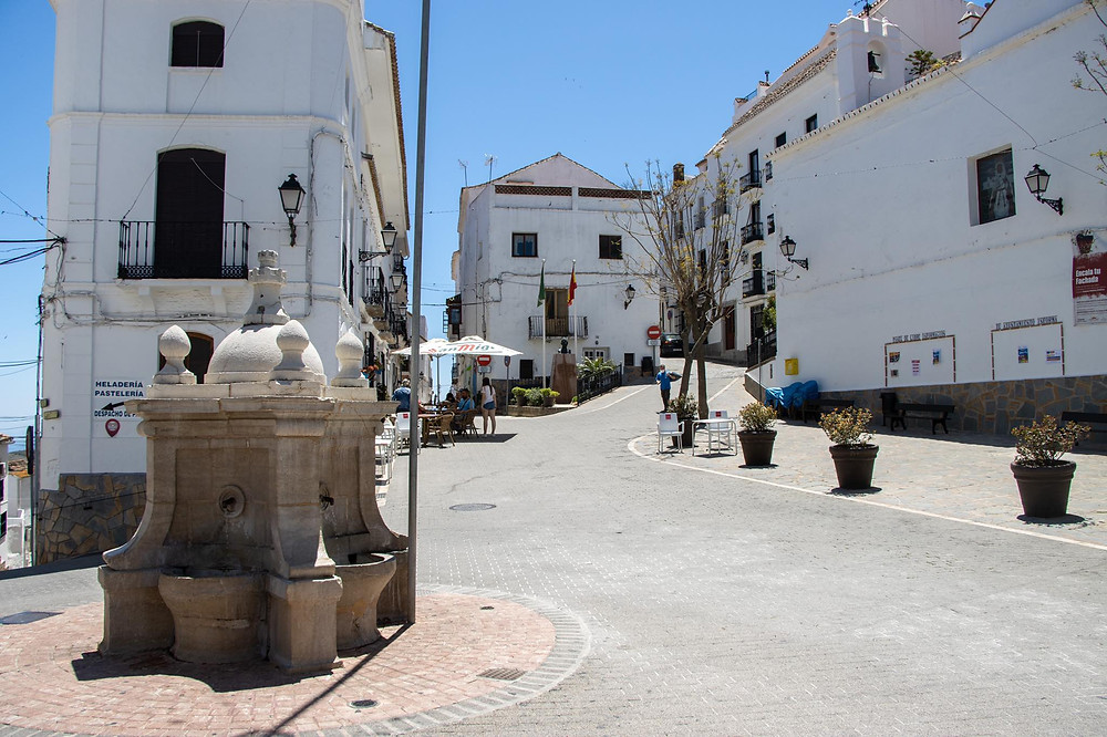 Historic fountain in the middle of a small plaza surrounded by white buildings.