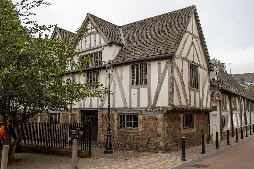 Medieval building in white and wooden beams on the corner of a street.