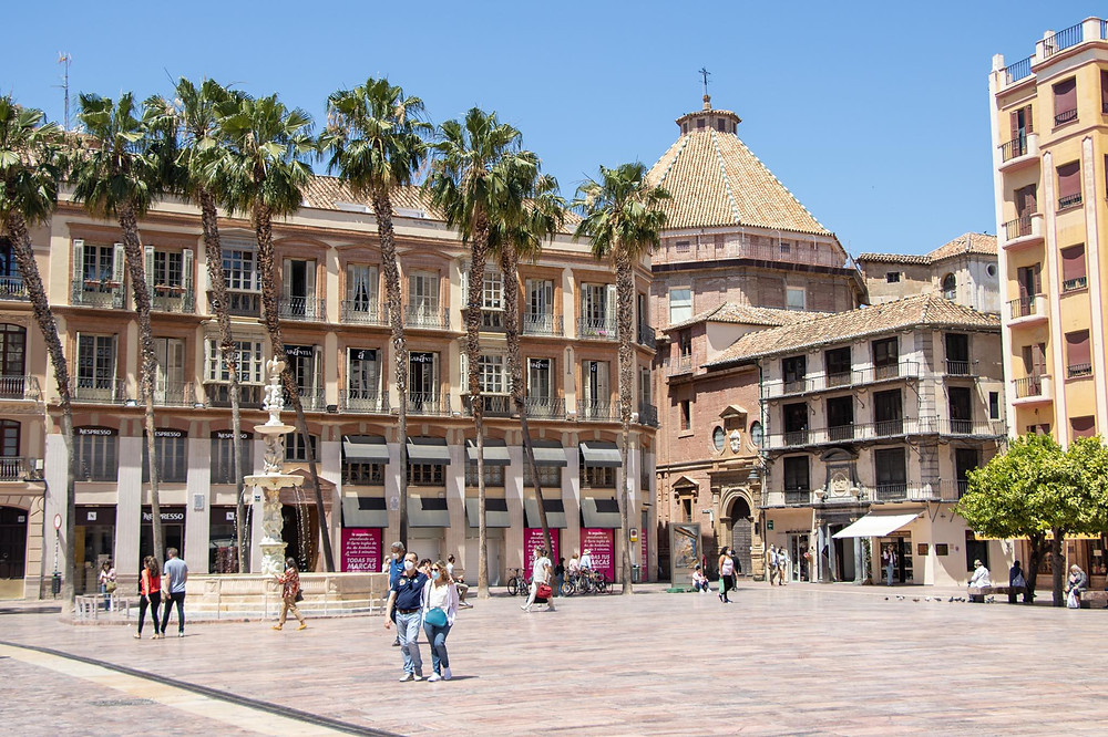Large open tiled plaza in Málaga with a fountain and palm trees.