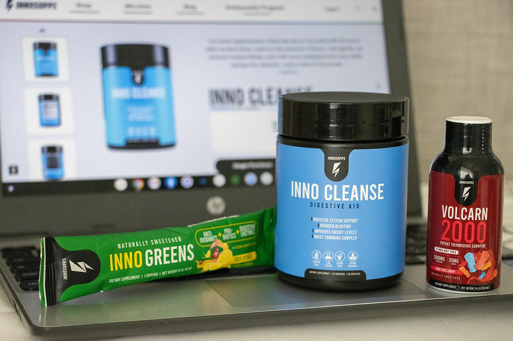 Selection of supplement products in front of a computer screen with Inno Supps on it.