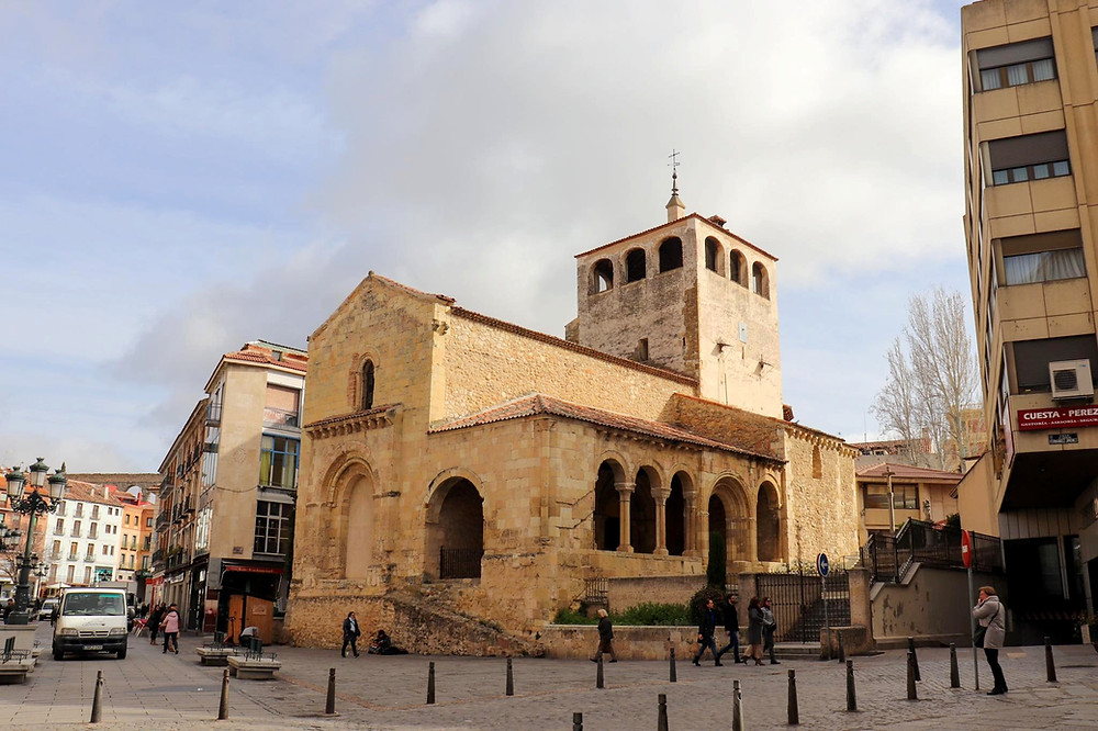 Romanesque style church in yellow brick on a street in Segovia with a square tower.