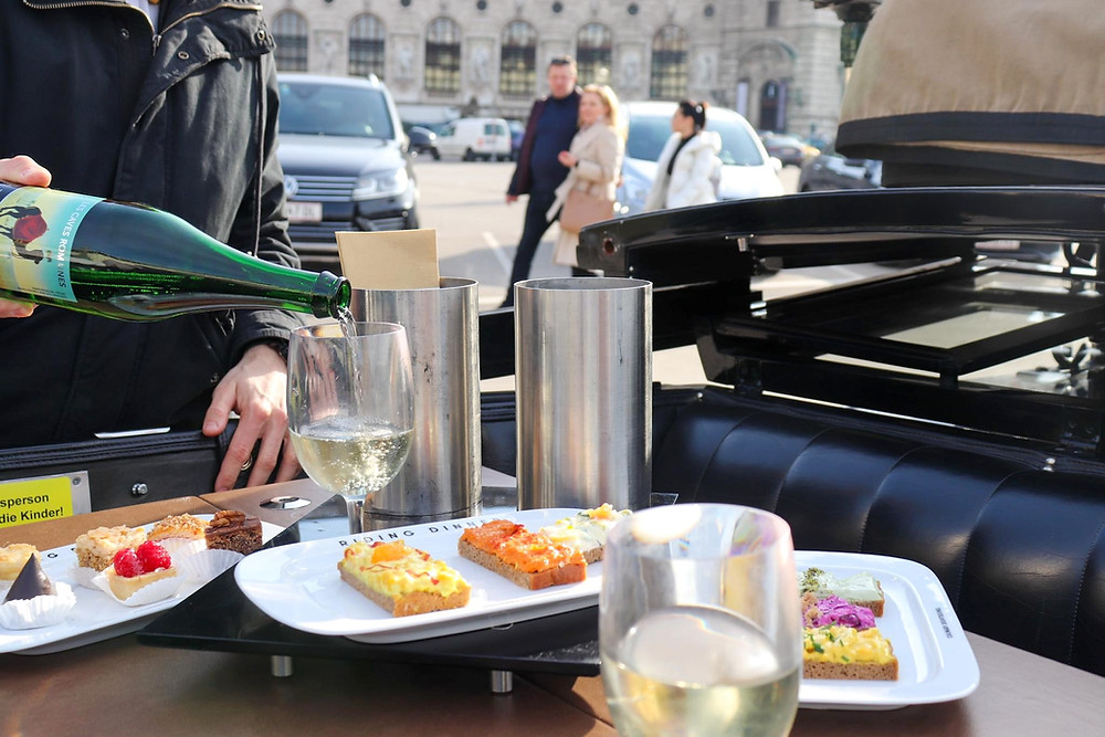 Small sandwiches, glasses, wine bottle being poured, and the seat inside the carriage, food and drinks sit on a table in the middle.