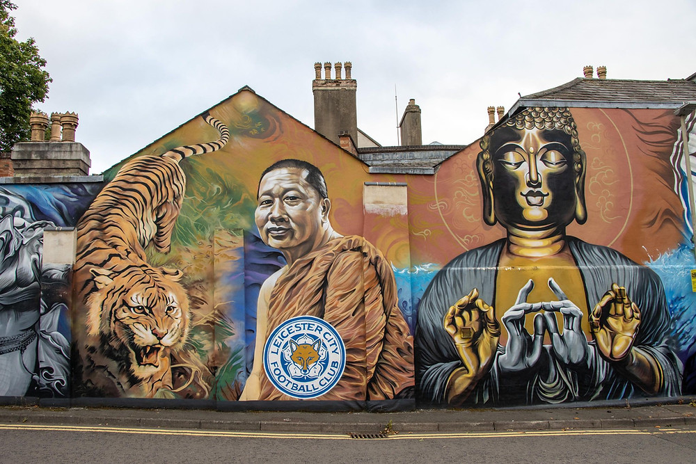 A wall mural with a monk, buddha, tiger, and football logo on it.