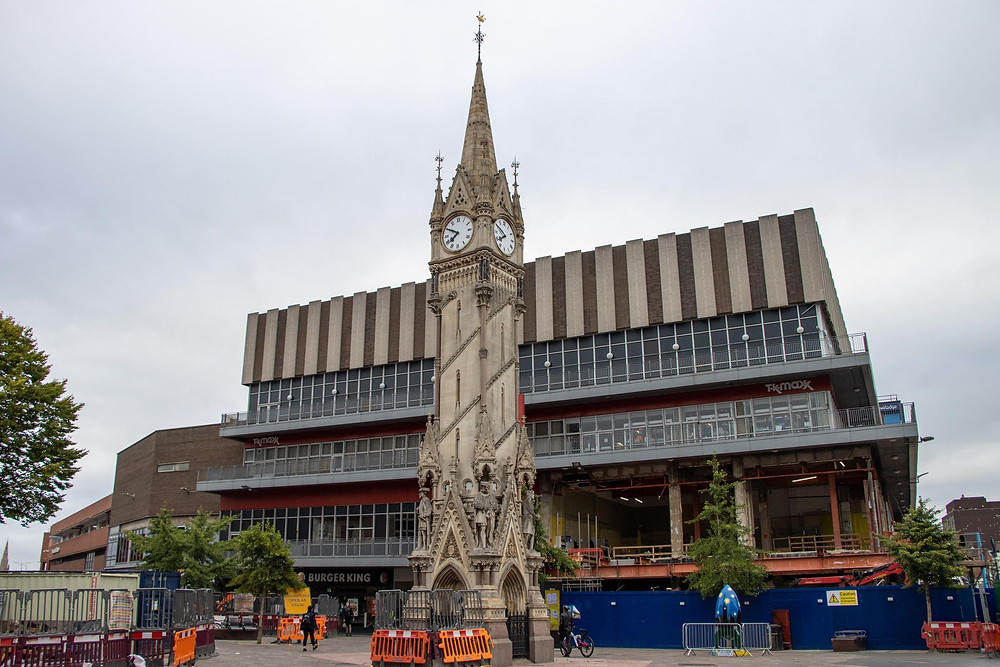 Long clock tower with a pointed top in the middle of the city centre.