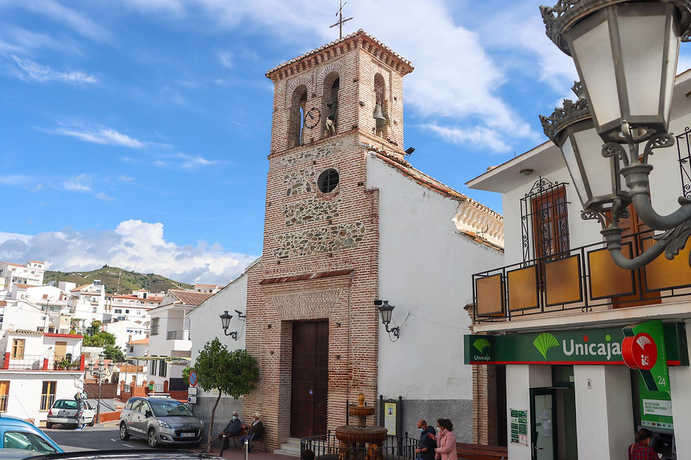 Orange bricked church tower with white walls on either side.