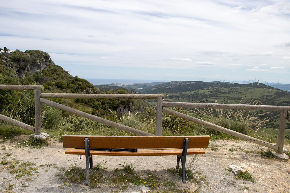 Bench at a high viewpoint overlooking the hills with the sea in the distance.