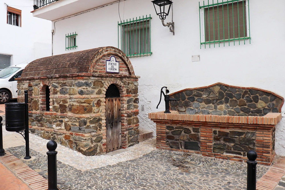 Old water fountain against a white wall made of large stones and bricks. A small hut is next to it built in the same way with an arched roof.