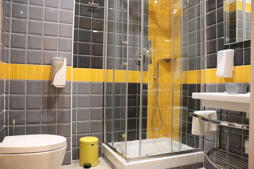 Yellow and grey tiled bathroom in B&B Via Toledo 156 Naples Italy