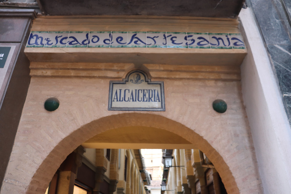Entrance to the Alcaiceria Market with tiled Arabic writing in Granada Spain