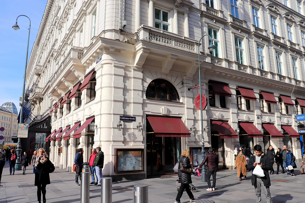 Outside of Hotel Sacher from the corner - a white architectural building with red sun blockers over the windows.