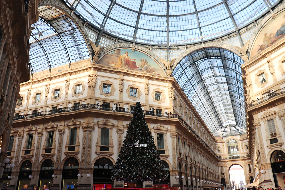 The interior of Galleria Vittorio Emanuele II during the day with a giant Christmas tree in the centre, one of the few free things to do in Milan.