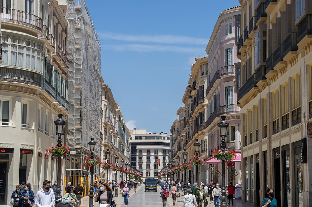 Main shopping street in Málaga lined with Gothic buildings and people walking.