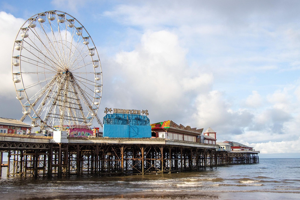 An old pier lined with arcade games and rides with a large Ferris Wheel in the centre.