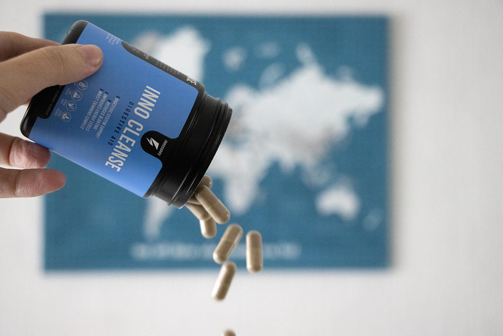 Supplement bottle with the pills being spilt out into the air in front of a map on the wall.