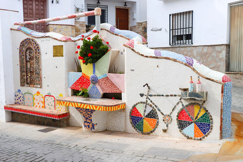 Small colourful tiles on a white wall creating a bicycle with bottles on the back and a seating area.