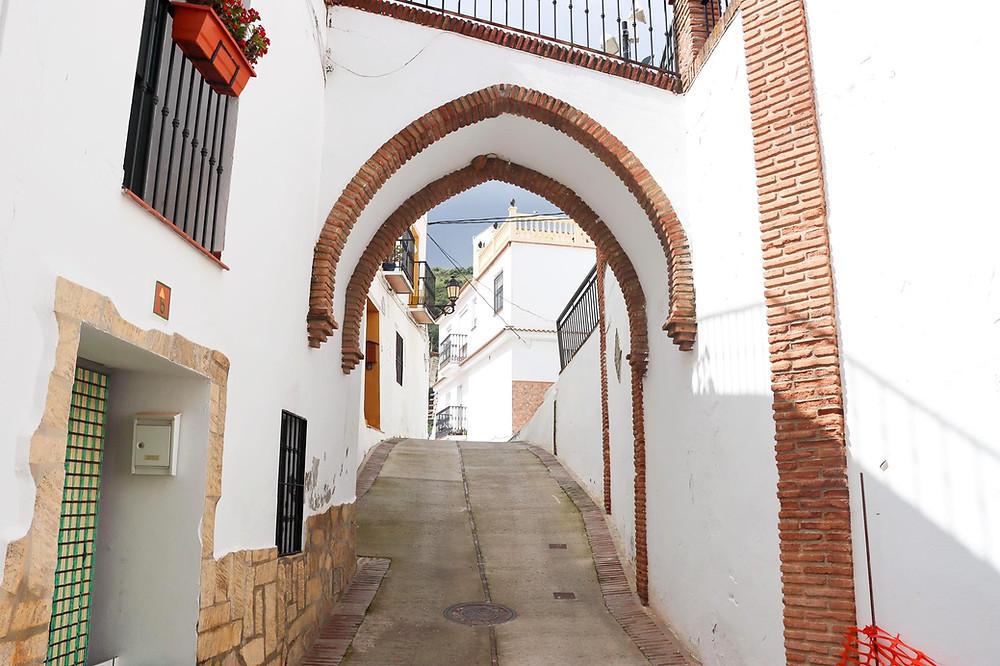 Whitewashed arch connecting two houses, trimmed with brown bricks.