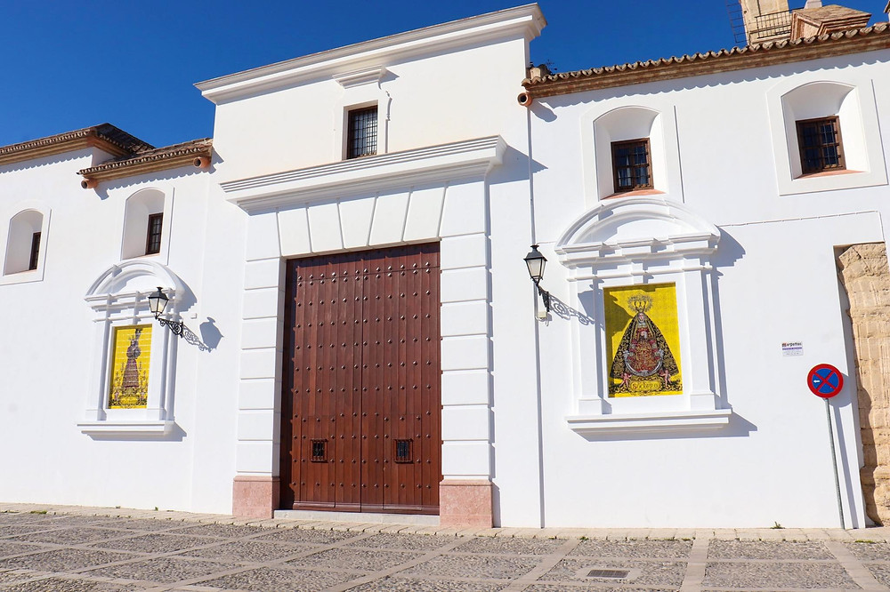 Iglesia de Santa María de Jesús from the side with white washed walls, a large brown studded door, and religious murals on either side of the door in Antequera.