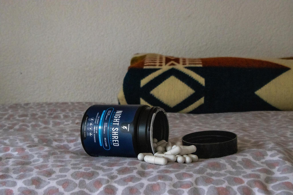 Navy supplement pill bottle open on its side on a bed with pink sheets with the pills spilling out of it.