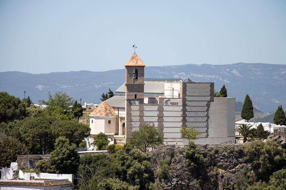 View of a historic church with a tower from a viewpoint in a white village.
