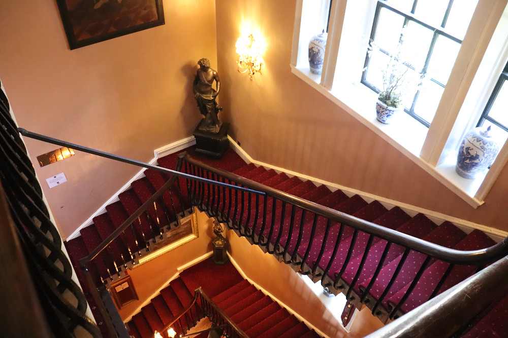 Red carpeted stairs leading up to the room inside lumley castle hotel northern england