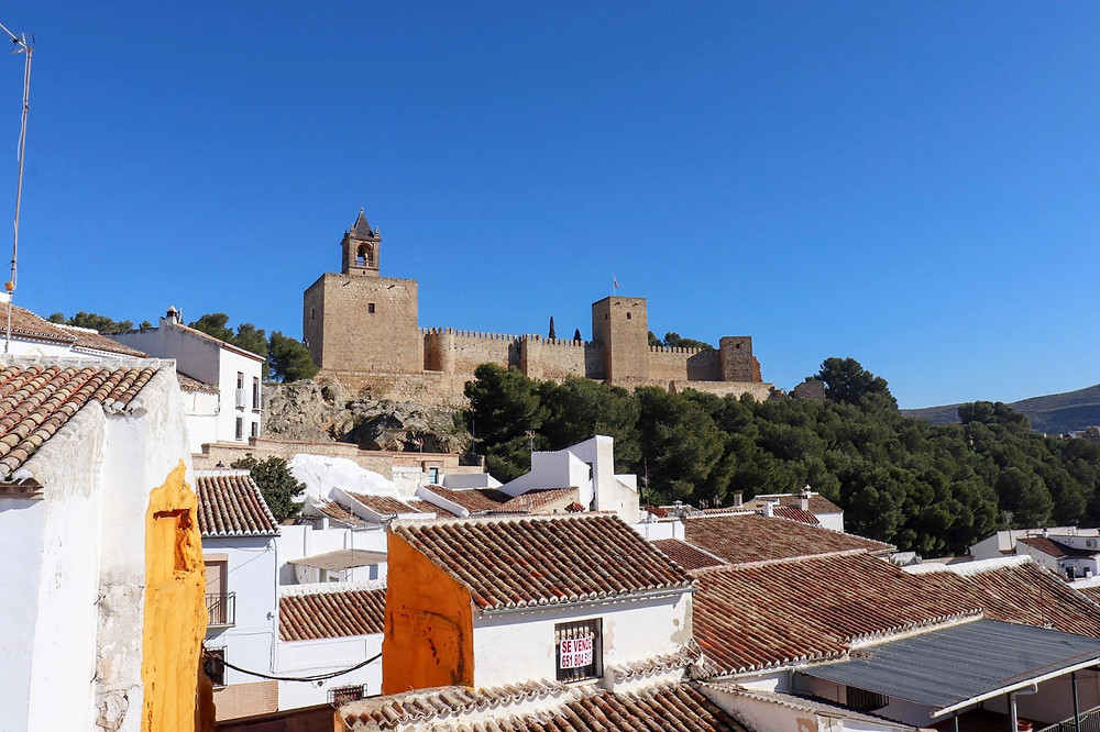 View of Alcazaba de Antequera on the hill from above the rooftops on a sunny day.