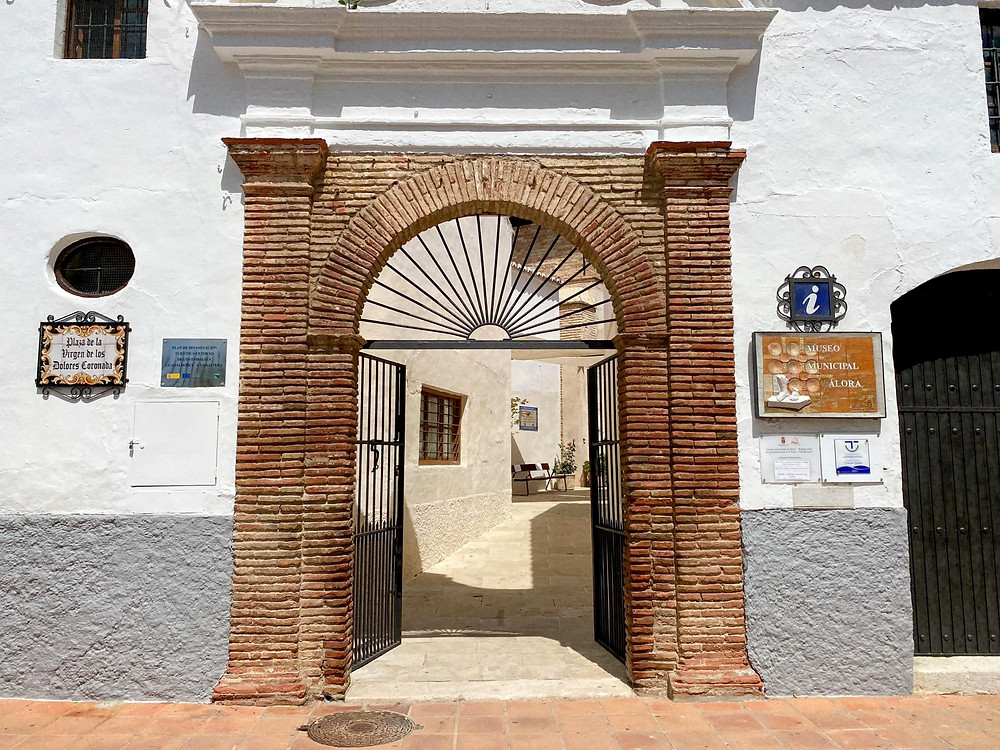 Brick arch set into a white wall with a railed gate in the centre.