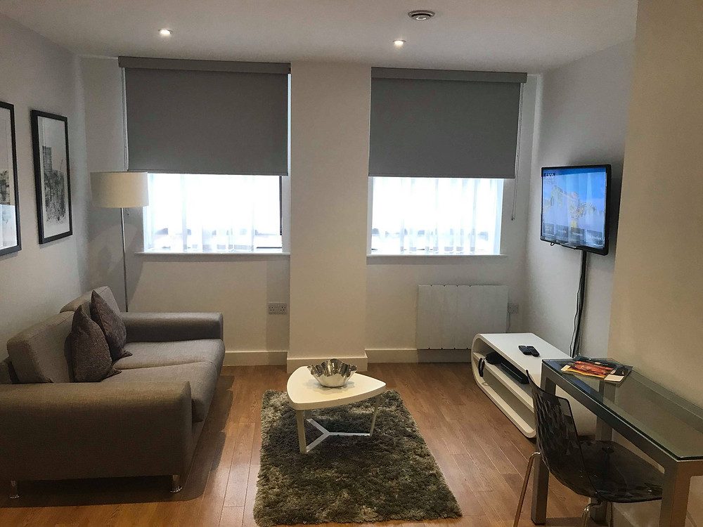 Living room area with television and couch inside SACO Apartments Manchester England