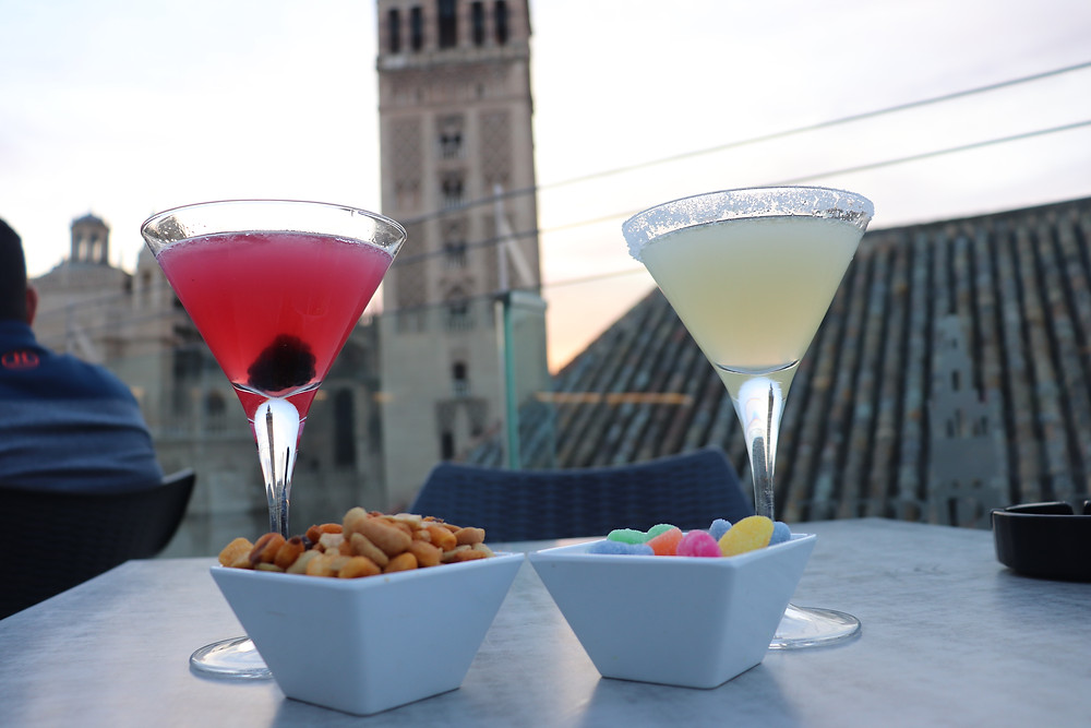 Cocktails and nibbles overlooking seville cathedral at sunset, spain
