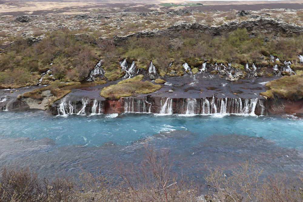 Hraunfossar Waterfall clear blue water in Iceland