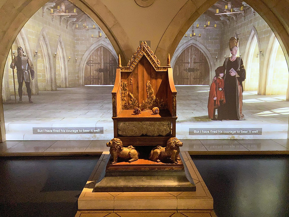 Wooden king's throne in front of arched screens showing people in period dress.