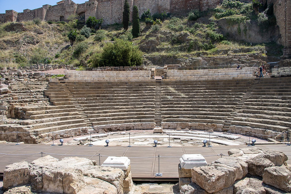 Roman theatre in ruins, slightly below ground in front of an Arab fortress.