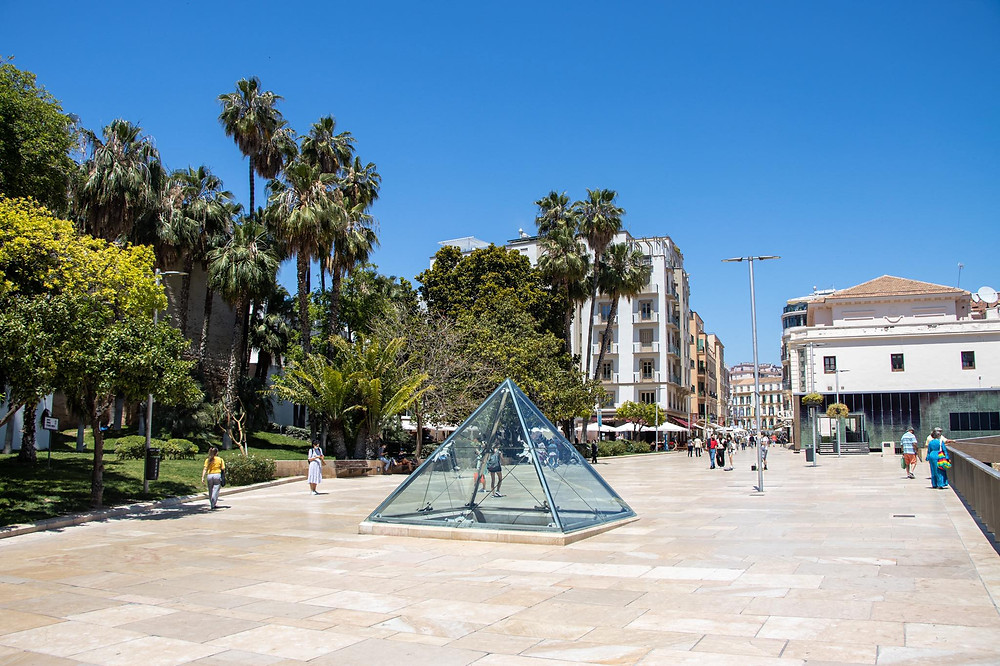 Small glass pyramid in the middle of a pedestrian street, surrounded by trees.