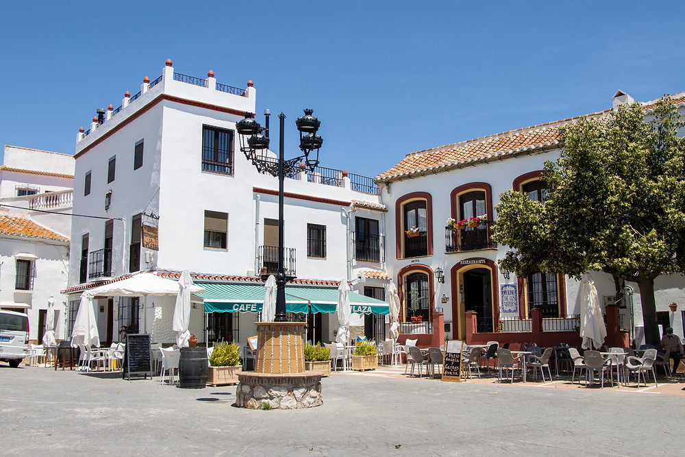 Small plaza in the white village with two restaurants in the corner and a lamp post in the centre.