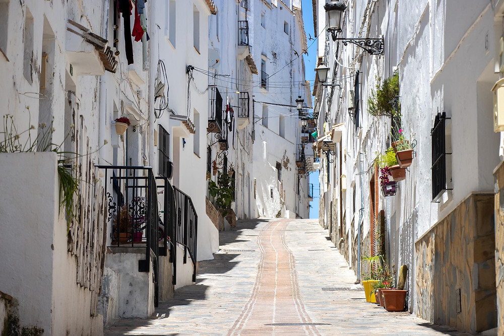 Whitewashed street lined with tall houses going up a hill.