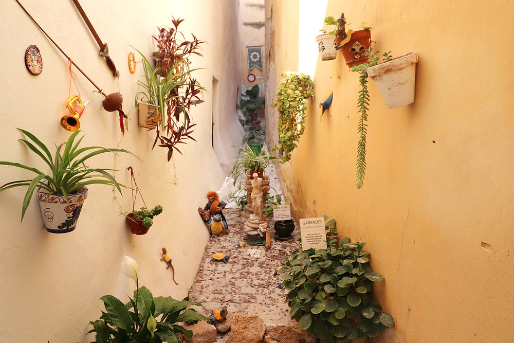 Street with plants and small trolls in Cadiz, Spain