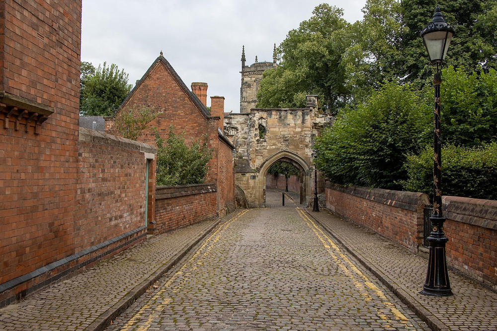 Small medieval entry gate on a cobbled street with a church tower in the background.
