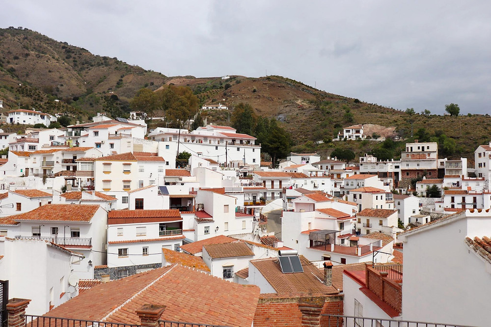 Viewpoint over the top of whitewashed houses with orange roofs, hills rise up behind them.
