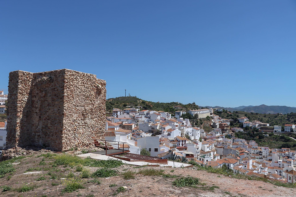 View of the whitewashed village from the top of a hill with a small historic tower on the top of it.