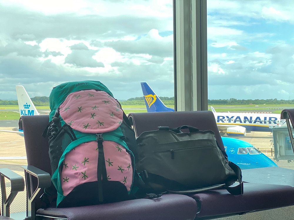 Departure lounge with bags overlooking runway in terminal 3 at Manchester Airport
