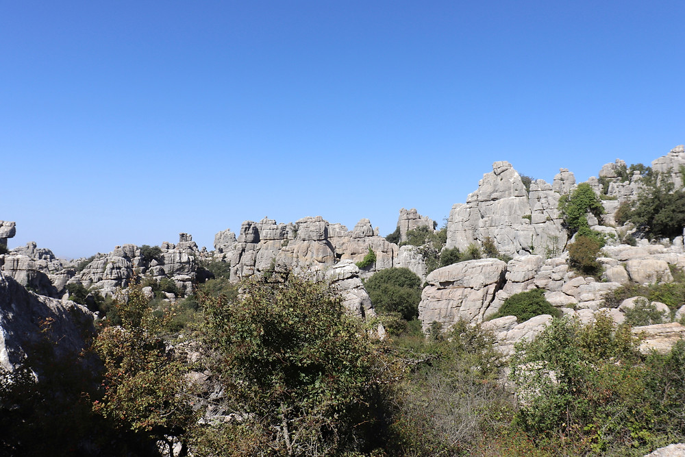 View of limestone rock formations like stacks of flat stones rising into tall pillars.