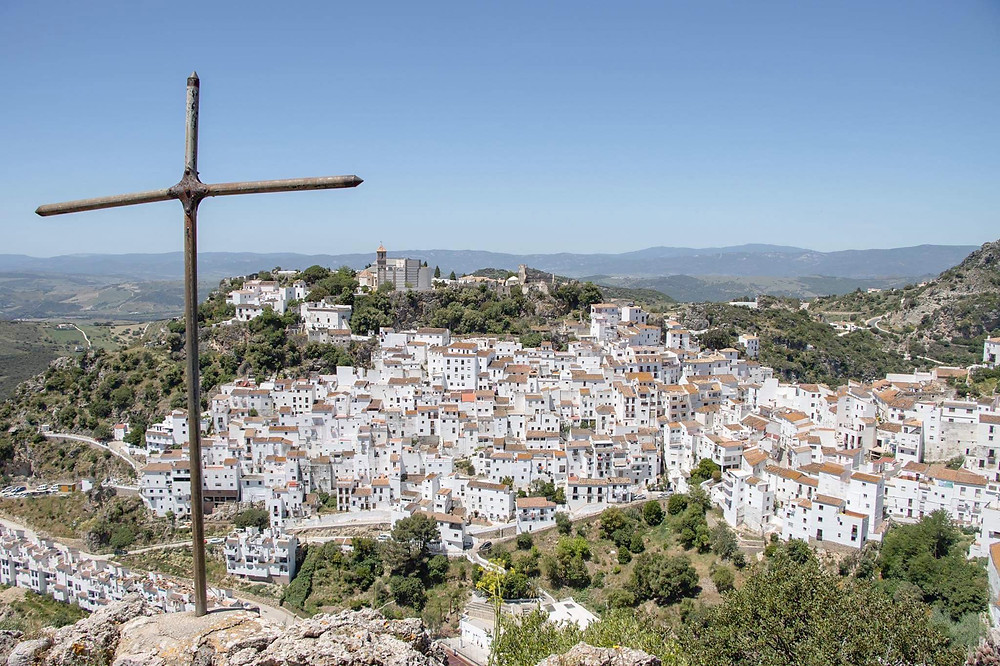 View of a white village from the top of a hill with an iron cross in the foreground.