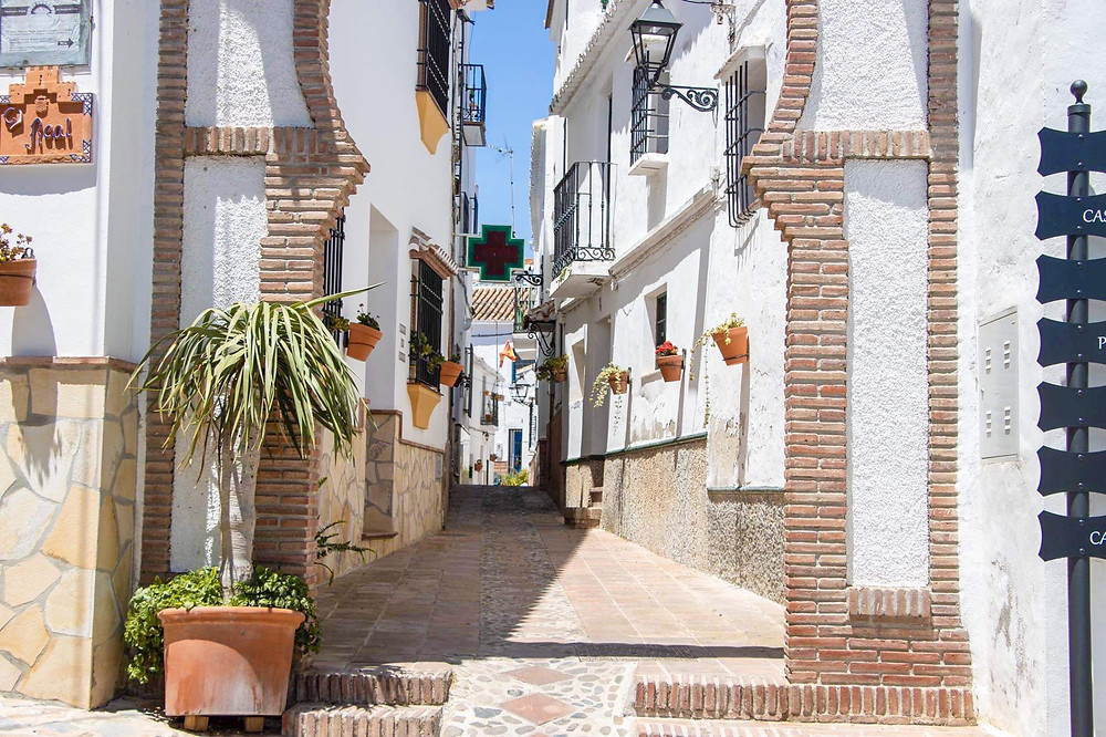 Arab arched street entrance of a white village with the street being lined with flower pots on the walls.