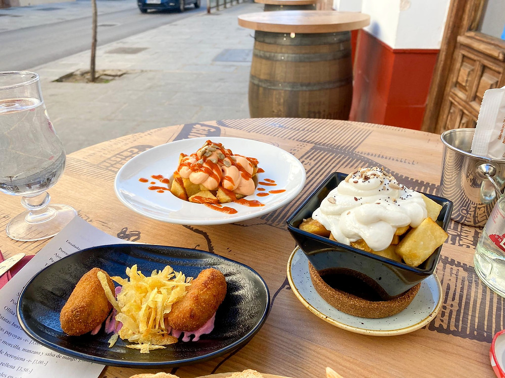 Selection of three tapas dishes from Arte de Tapas in Antequera - croquettes, patatas bravas, and chips covered in a cheese white sauce.