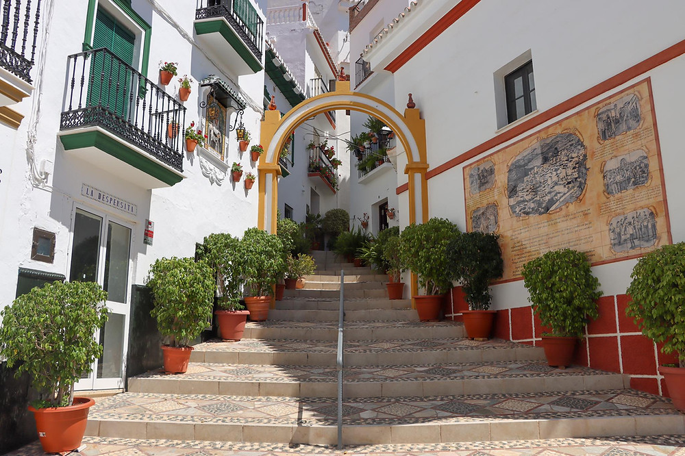 A decorated staircase next to a plaza painted in yellow with bushes lining it.