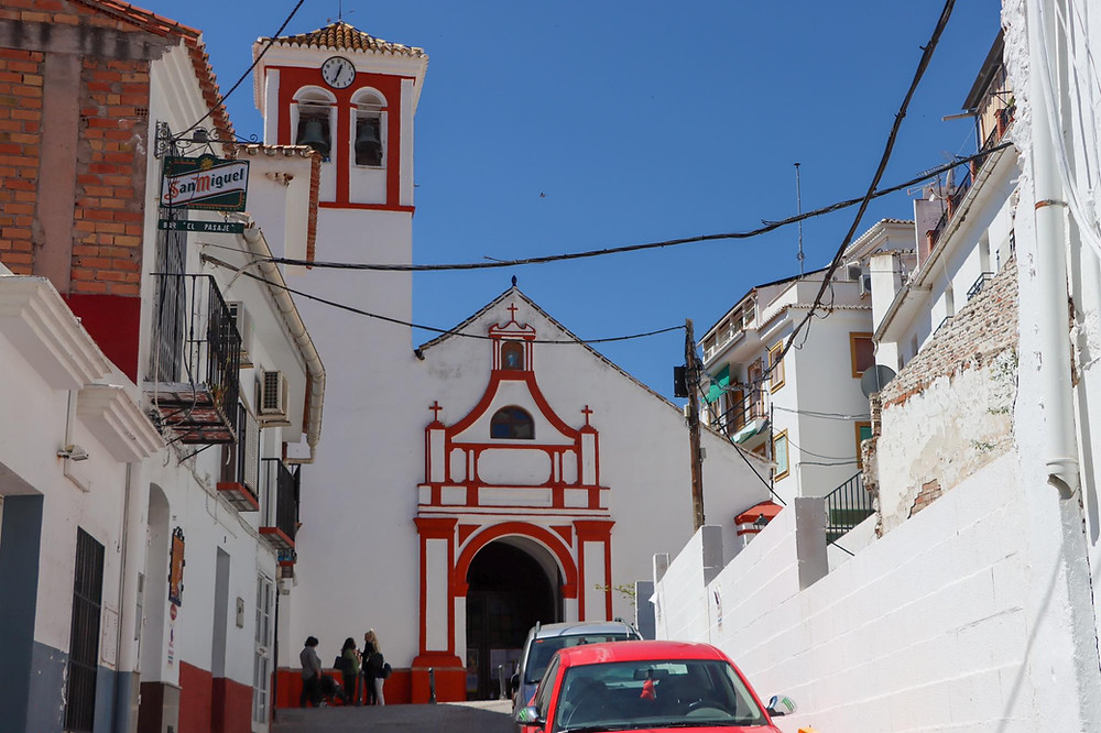 View of a white church at the end of a narrow street, trimmed in red paint.