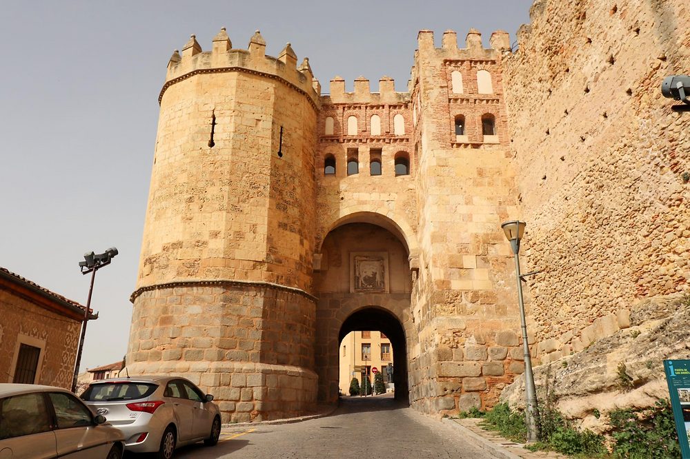 Massive entrance gate to the city with a tower on the left and a road leading through it.