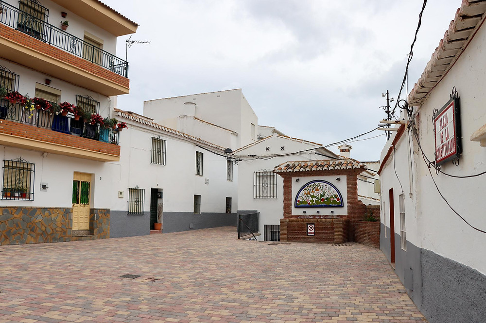 Small plaza surrounded by white walls and a tiled fountain at the far end.