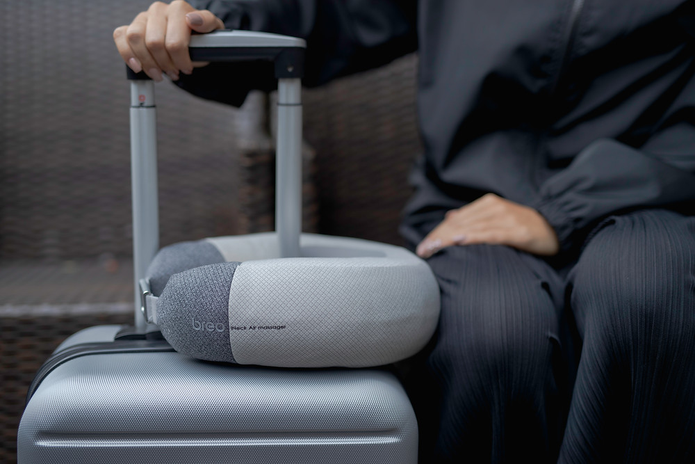 iNeck air2 heated neck massager sitting on a grey suitcase with a person next to it